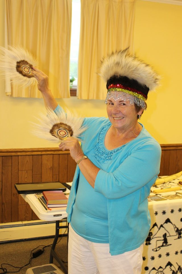 Judy showing how the hand fan and head dress is worn for dancing.